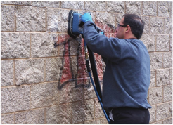 A maintenance technician uses proprietary cleaning and containment equipment to remove a tag from a split-faced black wall protected  with a two-component urethane/acrylic clearcoat. Photo courtesy af Surtec Inc.